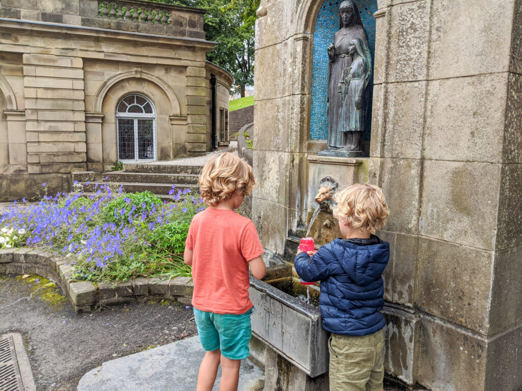 filling up bottles with fresh spring water at St Anne's Well, Buxton